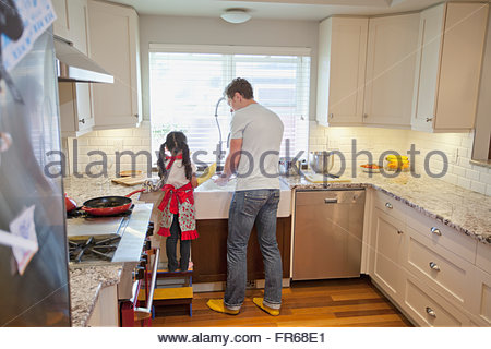 dad and young daughter doing dishes together - Stock Photo