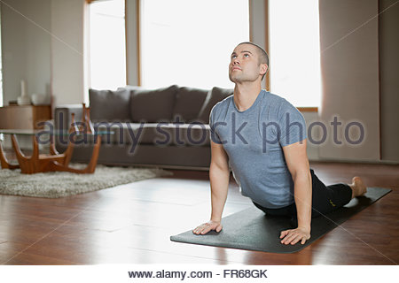 man doing yoga poses at home - Stock Photo