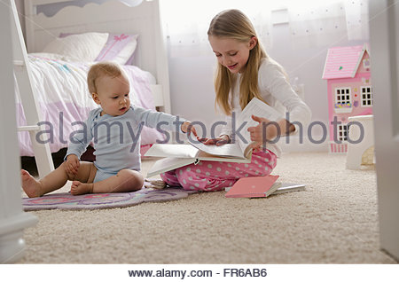 sister reading with younger brother in bedroom - Stock Photo
