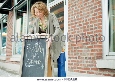 small business owner prepping to open - Stock Photo