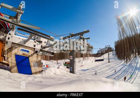 Chairlift in 'Krasnaya Glinka' mountain ski resort in winter sunny day in Samara, Russia