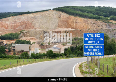 Warning Sign at the entrance road to a open quarry in mountain of the Belgian Ardennes - Stock Photo