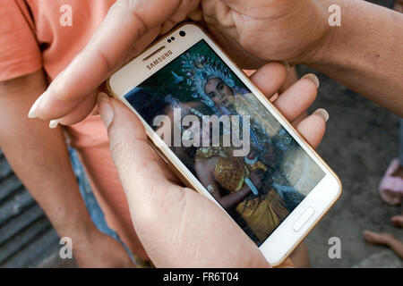 A Cambodian man who is an actor living in poverty looks at a photo on a Samsung smartphone in a slum in Kampong - Stock Photo