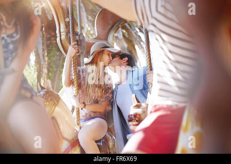 Young couple kissing on carousel at amusement park - Stock Photo