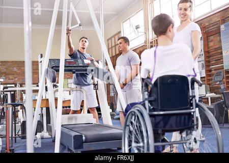Physical therapists preparing treadmill for man in wheelchair - Stock Photo