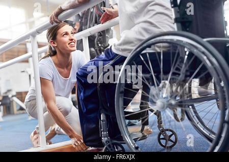 Physical therapist preparing man in wheelchair - Stock Photo