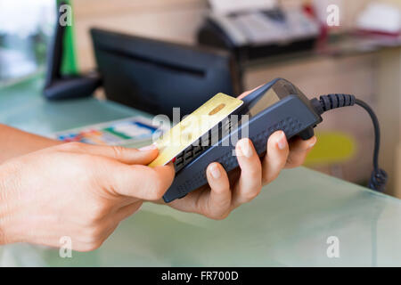 Woman paying with NFC technology on credit card in shop. Contactless payment - Stock Photo