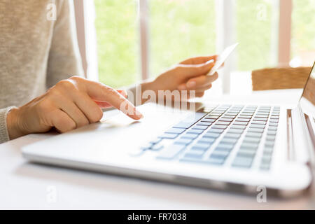 Woman at home using credit card and laptop. Shopping online - Stock Photo