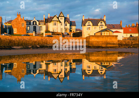 20/03/2016, The sun sets on a row of houses reflected in the water at Elie, a coastal town in the East Neuk of Fife, - Stock Photo