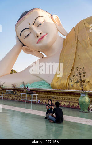 Burmese tourists take selfie in front of the Myathalyaung Reclining Buddha in Bago, Burma (Myanmar) - Stock Photo