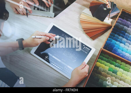top view of two colleagues interior designers discussing data with digital tablet and new modern computer laptop - Stock Photo