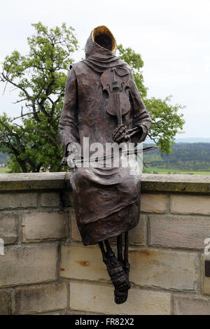Monk Maurus with a violin sitting on the wall around the church in parish church of St. James in Hohenberg, Germany - Stock Photo