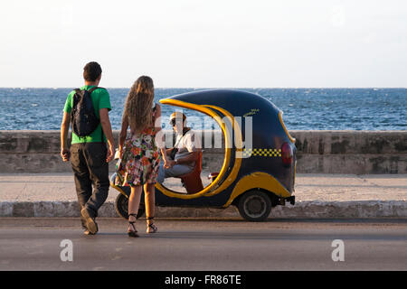 Daily life in Cuba - young couple crossing road to approach local man in cocotaxi, coco taxi, at El Malecon, Havana, - Stock Photo
