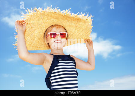 Fun on white sand. Portrait of happy girl in striped swimsuit and big straw hat against blue sky - Stock Photo