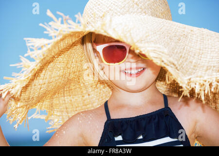 Fun on white sand. Portrait of happy girl wearing big straw hat - Stock Photo