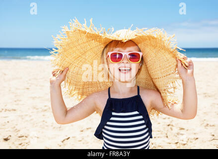 Fun on white sand. Smiling girl in striped swimsuit and big straw hat on a white beach - Stock Photo