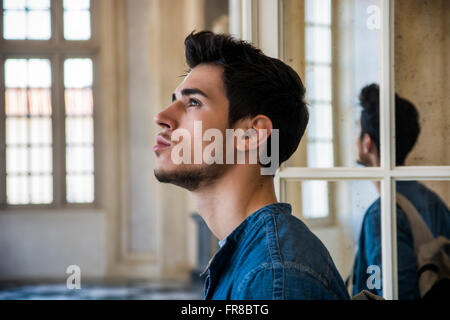 Half Body Shot of a Thoughtful Handsome Young Man Looking Away out of Window, Inside Historic Building in European - Stock Photo