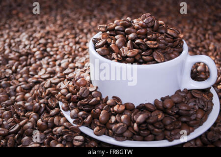 whole roasted coffee beans in bowl and glass and wood table - Stock Photo