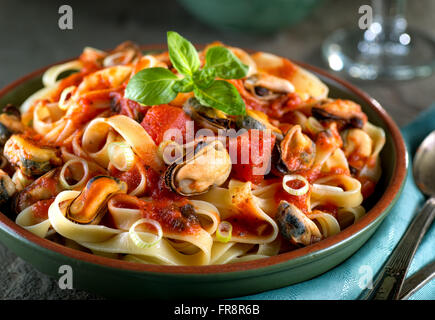 Delicious pasta with mussels in basil marinara sauce. - Stock Photo