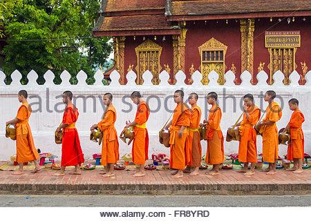 Buddhist novice monks receive alms (Tak Bat) in front of Wat Sene Souk Haram temple, Luang Prabang, Louangphabang - Stock Photo