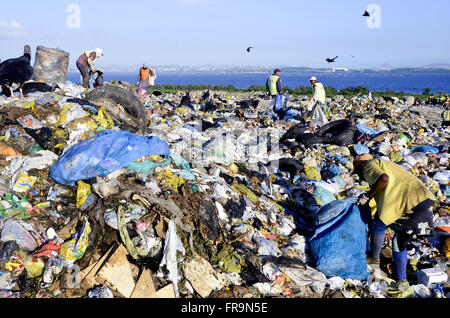 Scavengers collecting recyclable waste at the Sanitary Landfill of Jardim Gramacho - Stock Photo