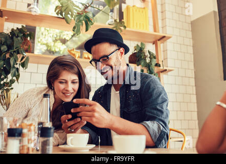Portrait of young friends sitting in cafe looking at the photos on mobile phone. Happy young people meeting in a - Stock Photo