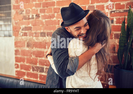 Portrait of young man embracing his girlfriend at cafe. Young man hugging a woman in a coffee shop. - Stock Photo
