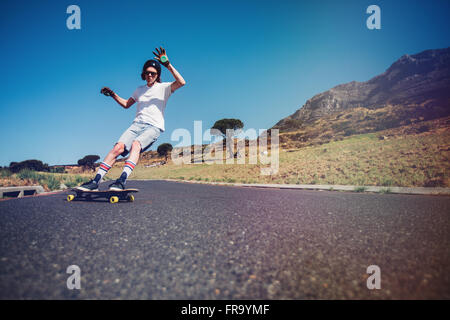 Young man longboarding on a road. Young guy wearing protective gear skating on rural road. - Stock Photo
