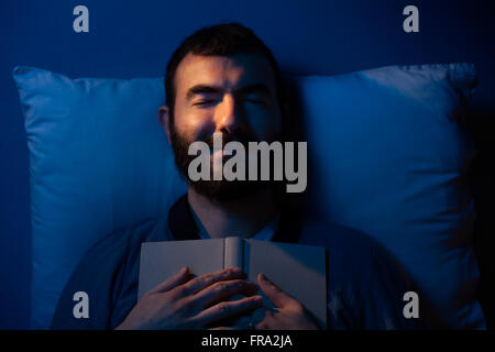 Smiling Man Sleeping with a Book on His Chest - Stock Photo