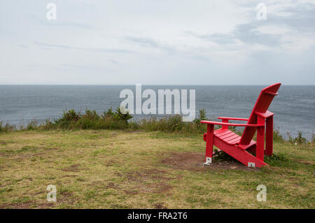 red muskoka chair overlooking Atlantic Ocean in nova scotia canada - Stock Photo