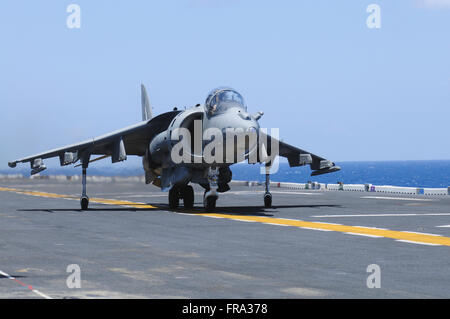 An AV-8B Marine Harrier II lands on the flight deck of the USS Peleliu (LHA-5) during flight operations in the Pacific - Stock Photo