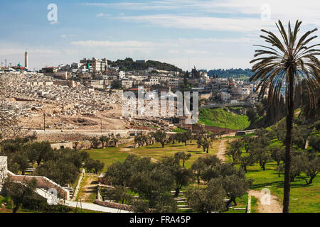 Absalom's tomb and graves in a cemetery; Jerusalem, Israel - Stock Photo