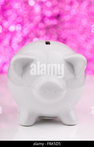 White piggy bank on pink background - Stock Photo