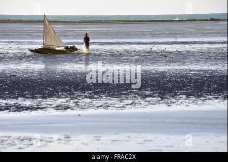 Pescador e seu barco na Praia de Japaratinga - Stock Photo