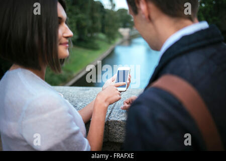 woman showing something to friend on her phone - Stock Photo
