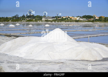 Lot of salt in saline drying of Praia Seca in Araruama Lake with windmills in the background - Stock Photo