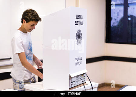 Teen voter voting in electronic urn at PUC-Rio - Elections 2014 - Stock Photo
