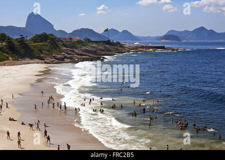 Bathers on the Beach Devil in Ipanema and Copacabana Fort in the background - Stock Photo