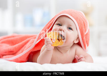 Cute baby with teether under a hooded towel after bath - Stock Photo