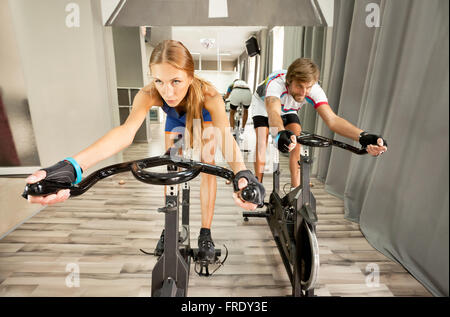 Young beautiful woman and a man working out determined in a modern cycling gym. - Stock Photo
