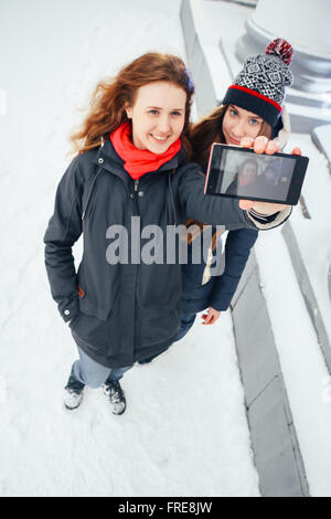 Two beautiful girls doing selfie  on white background Stock Photo