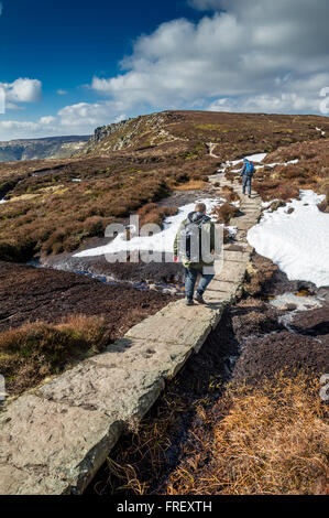 Men walking along stone slabs towards Crowden Tower on the Pennine way in the Peak District, Derbyshire, England, - Stock Photo