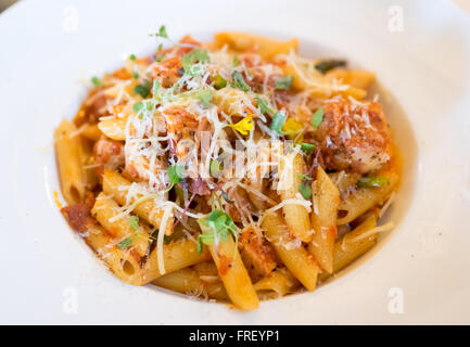 A plate of penne pollo (chicken) pasta in a tomato and red pepper sauce with Parmigiano Reggiano, boar bacon, and - Stock Photo
