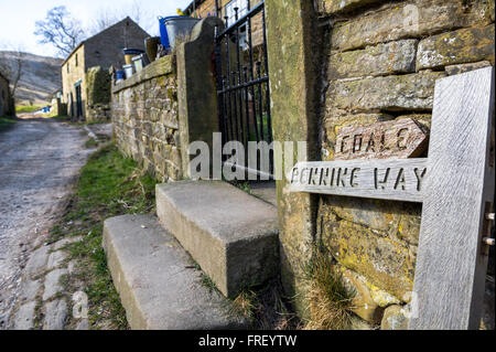 Wooden sign post showing direction to the Pennine Way from Edale outside a stone built farm house in the Peak District. - Stock Photo