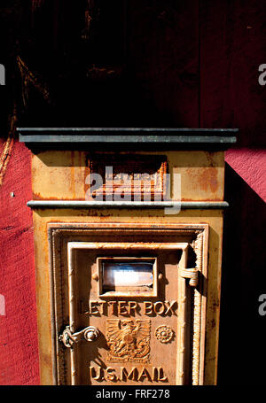 An old metal letter box on the wall of a red barn in Temple, New Hampshire, USA. - Stock Photo