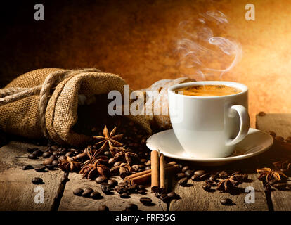 Cup of coffee and spices on wooden table - Stock Photo