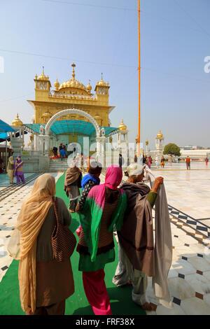 Traditionally dressed women and other Sikh pilgrims outside the historic Tarn Taran Gurdwara in Punjab India - Stock Photo