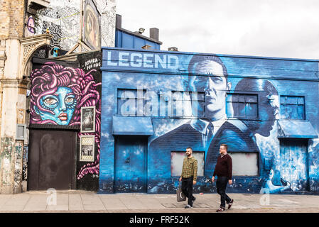 Two middle aged men walking in front a piece of street graffiti promoting the release of the Krays' Legend. - Stock Photo