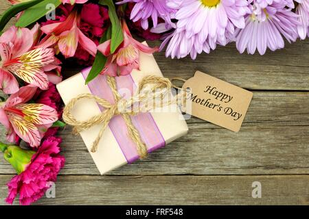 Border of flowers with gift box and Happy Mother's Day tag against a rustic wood background - Stock Photo