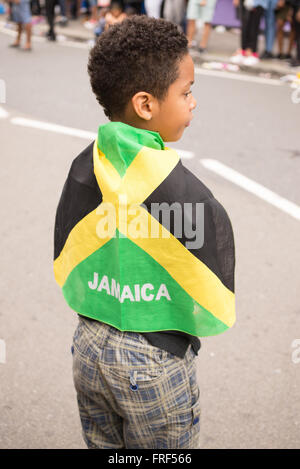 Afro-american Boy wrapped in a Jamaica flag during the street parade for the Notting Hill Carnival - Stock Photo